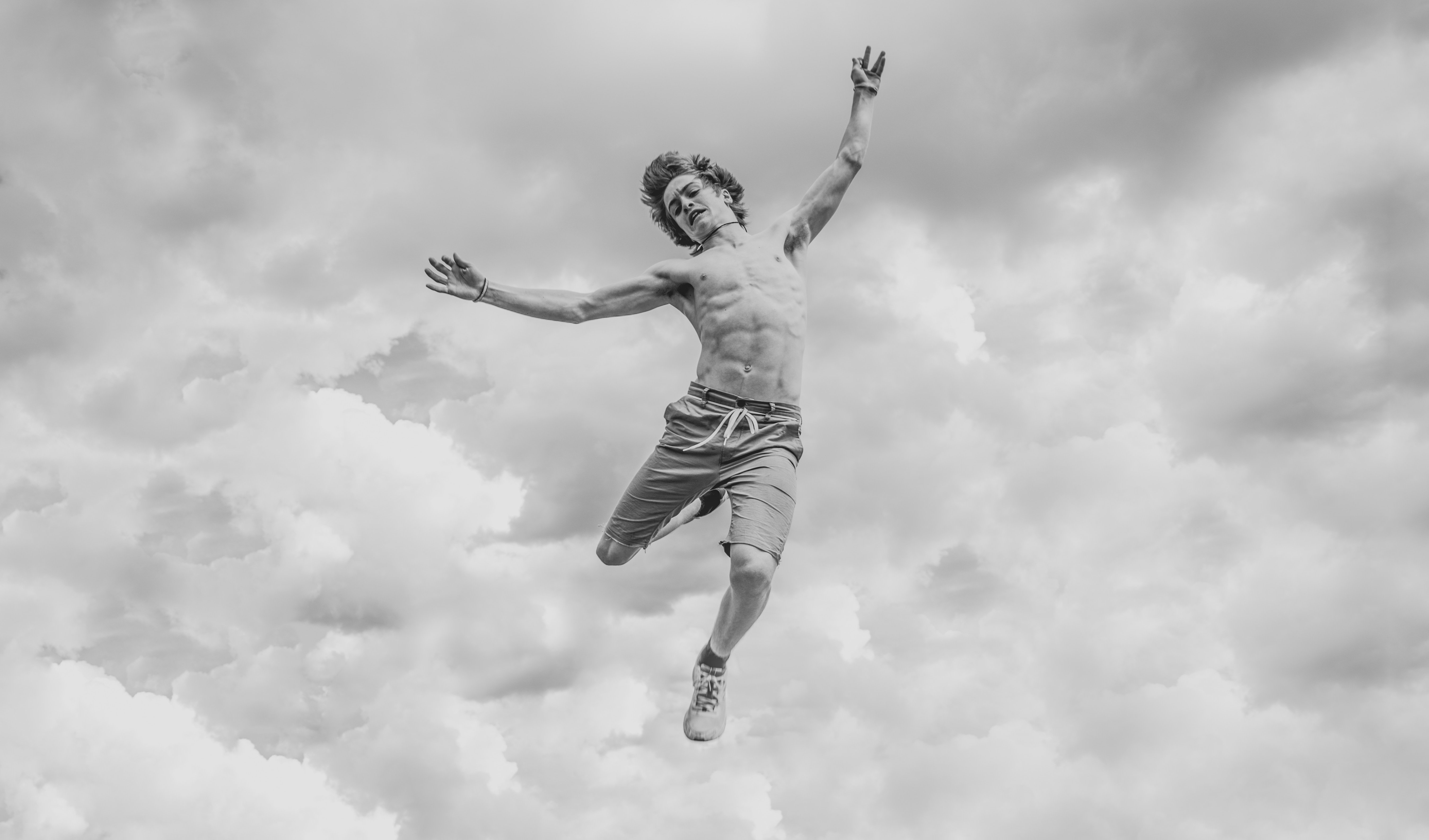 Image of a man jumping in the air, with no shirt. Live
